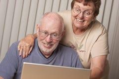 Pares adultos mayores emocionados que se divierten en el ordenador Fotos de archivo