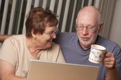 Pares adultos mayores felices que se divierten en el ordenador Foto de archivo
