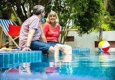 Pares adultos mayores que disfrutan del tiempo de verano en la piscina junto Imágenes de archivo libres de regalías