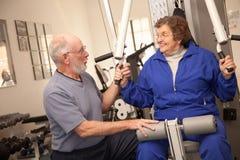 Pares adultos mayores que se resuelven junto en el gimnasio Fotografía de archivo