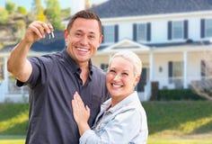 Pares adultos novos entusiasmado com chaves da casa na frente da casa bonita imagens de stock royalty free