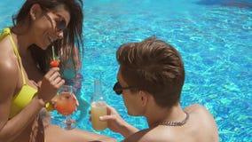 Pares adultos novos que flertam e que falam na piscina e nos cocktail bebendo Festa na piscina do verão Disparado em 4k video estoque