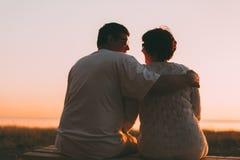 Pares adultos que abraçam no por do sol e no mar Imagem de Stock