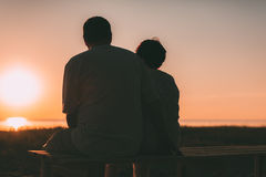 Pares adultos que abraçam no por do sol e no mar Imagens de Stock Royalty Free