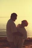 Pares adultos que abraçam no por do sol e no mar Imagem de Stock Royalty Free