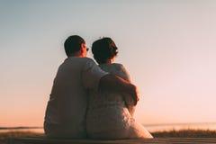 Pares adultos que abraçam no por do sol e no mar Imagens de Stock
