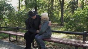 Pares adultos que abrazan en un banco de parque almacen de video