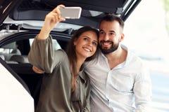 Pares adultos que eligen el nuevo coche en la sala de exposición fotos de archivo libres de regalías