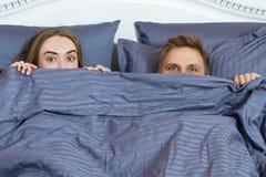 Pares adultos que escondem sob a cobertura na cama Pares no quarto na manh? imagens de stock royalty free