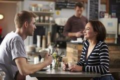 Pares adultos que hablan en una tabla en una cafetería, vista lateral fotos de archivo libres de regalías