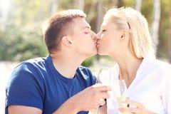 Pares adultos que se besan en la playa con champán imagen de archivo libre de regalías