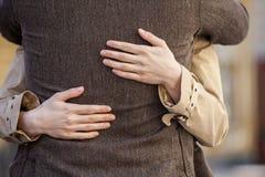 Pares adultos que se colocan en la calle y el abrazo Imagen de archivo