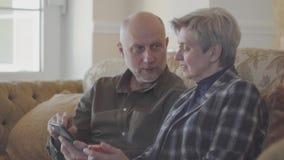 Pares adultos que se sientan en el sofá grande y el hombre calvo que muestran las fotos en el teléfono móvil para su mujer madura almacen de video