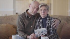 Pares adultos que se sientan en un sofá que muestra sus viejas fotos y partes sus memorias Movimientos del foco de la foto a un c almacen de video