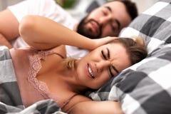 Pares adultos que sufren de problema que ronca en cama Fotos de archivo