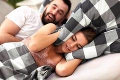 Pares adultos que sufren de problema que ronca en cama Foto de archivo
