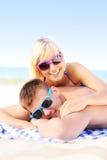Pares adultos que toman el sol en la playa Foto de archivo libre de regalías