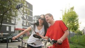 Pares adultos que toman Selfie después del montar a caballo de la bicicleta Un hombre sostiene un Monopod Ellos Sit On Bicycle metrajes