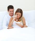 Pares afectuosos que comem a fruta em sua cama Fotografia de Stock