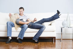Pares afectuosos que relaxam junto no sofá fotos de stock royalty free