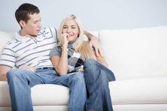 Pares afectuosos que relaxam no sofá imagens de stock