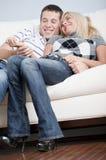 Pares afectuosos que riem e que relaxam no sofá fotografia de stock royalty free