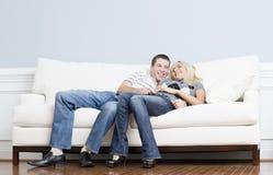 Pares afectuosos que riem e que relaxam no sofá imagem de stock royalty free