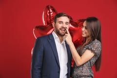 Pares afetuosos com abraço dos balões fotografia de stock royalty free