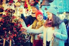 Pares afirmativos de la familia con la muchacha adolescente que elige deco de la Navidad Fotos de archivo