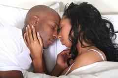 Pares africanos de Amrican en cama Imagenes de archivo