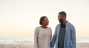 Pares africanos de sorriso que andam abaixo de uma praia junto no crepúsculo Fotos de Stock