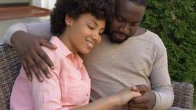 Pares africanos felices que abrazan en el banco, fecha al aire libre en café de la ciudad, proximidad almacen de metraje de vídeo