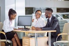 Pares africanos felizes com o carro de compra do negociante na feira automóvel ou no salão de beleza Foto de Stock Royalty Free