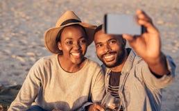Pares africanos jovenes felices que toman selfies juntos en la playa Imagenes de archivo