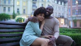 Pares africanos jovenes que abrazan en banco en la puesta del sol, fecha en parque de la ciudad, proximidad almacen de video