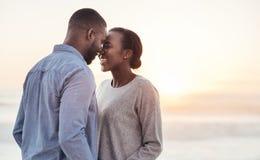 Pares africanos jovenes que disfrutan de un momento romántico en la playa Imagen de archivo libre de regalías