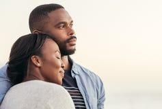 Pares africanos jovenes que disfrutan de una puesta del sol en la playa imagenes de archivo