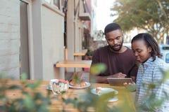 Pares africanos jovenes que hojean en línea en un café de la acera Imagenes de archivo