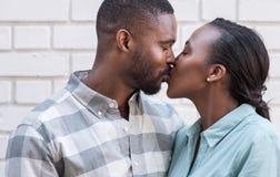 Pares africanos jovenes que se besan en la ciudad Fotografía de archivo libre de regalías