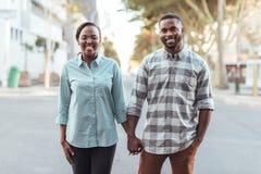 Pares africanos jovenes que sonríen mientras que lleva a cabo las manos en la ciudad Fotografía de archivo