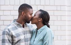 Pares africanos jovenes románticos que se besan en la ciudad Imagenes de archivo