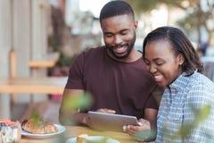 Pares africanos jovenes sonrientes que hojean en línea en un café de la acera Fotografía de archivo