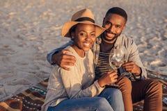 Pares africanos jovenes sonrientes que se sientan en el vino de consumición de la playa Fotografía de archivo
