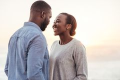 Pares africanos novos de sorriso que falam junto na praia Imagens de Stock Royalty Free