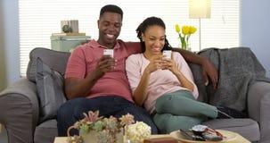 Pares africanos novos felizes que relaxam no sofá usando smartphones Fotografia de Stock Royalty Free