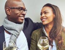 Pares africanos novos românticos que apreciam o vinho Fotografia de Stock Royalty Free