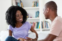 Pares africanos que falam e que flertam em casa imagens de stock