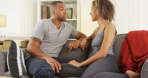 Pares africanos que falam junto no sofá Fotografia de Stock