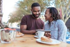 Pares africanos sonrientes que hojean en línea en una tabla del café de la acera Foto de archivo