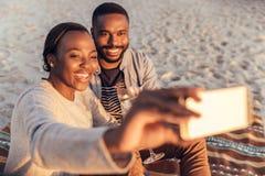 Pares africanos sonrientes que se sientan junto en la playa que toma selfies imagenes de archivo